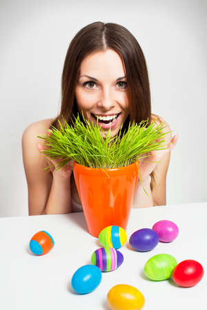 Excited woman searching for easter eggs in green grass