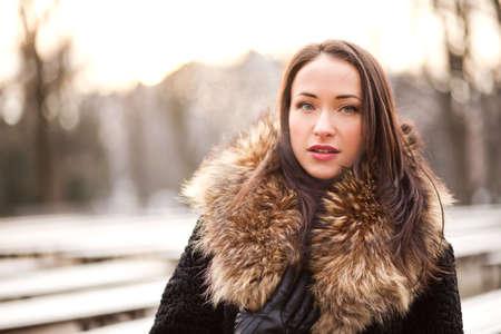 Beautiful lady is wearing a fur coat during the winter season Reklamní fotografie