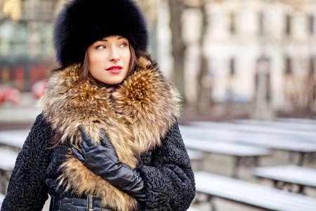 秋の高価な本物の毛皮および革の手袋を着て冬の女の子