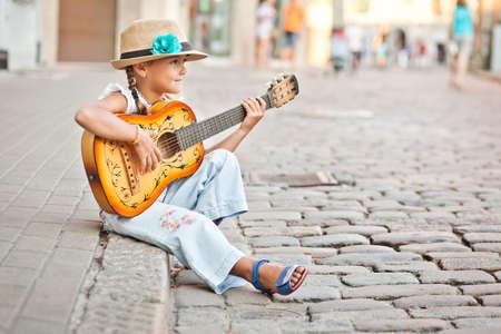 Girl playing guitar on the street Reklamní fotografie
