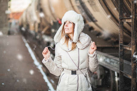 Pretty girl in winter blizzard on railroad station Reklamní fotografie - 35237142