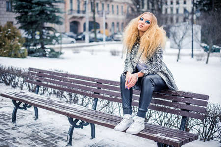 Golden haired woman on a bench Reklamní fotografie - 35856861