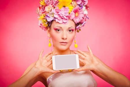 Spring flowers girl is holding smartphone in hands Reklamní fotografie - 36164471