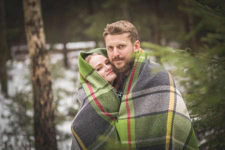 Young couple winter forest walk in a warm blanket Reklamní fotografie - 36123970
