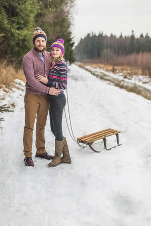 Young couple having a sled winter forest walk Reklamní fotografie - 36123971