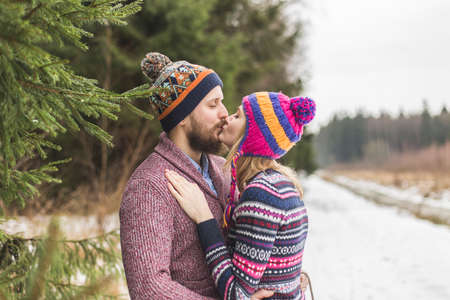 Young peaople are kissing in winter forest Reklamní fotografie - 36123973