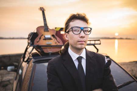 Hipter in glasses and his guitar on car rack Reklamní fotografie