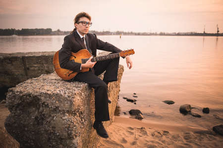 Male musician and his guitar on shore Reklamní fotografie - 36125340