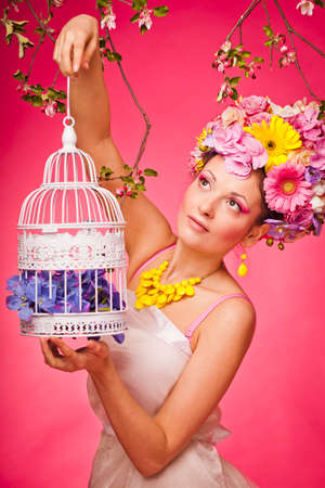 Spring portrait woman with a birdcage and flowers Reklamní fotografie - 38012725