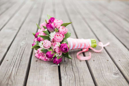 Pink and Purle tender flowers with ribbon on a wooden pattern Reklamní fotografie