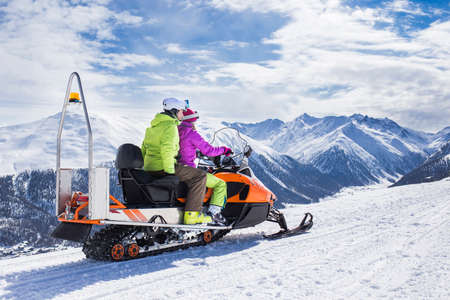 Men and his girlfriend having fun on a snowmachine sled on their vacation in alps