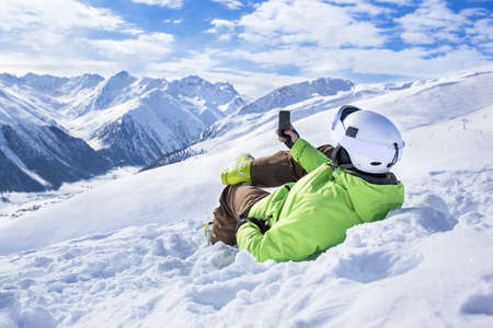 Happy successful man surfing mobile phone app at apine ski slope livigno italy resort village