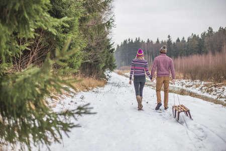 Happy couple pulling slaigh in winter snowy wood Reklamní fotografie
