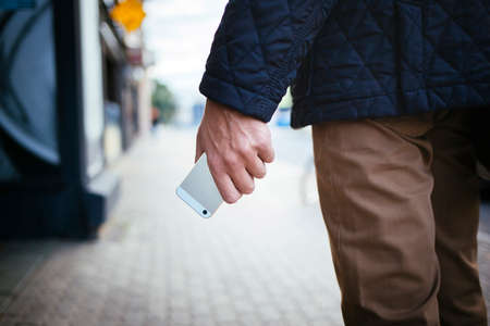 Cellphone in human palm on the city street blured background Reklamní fotografie - 56447478