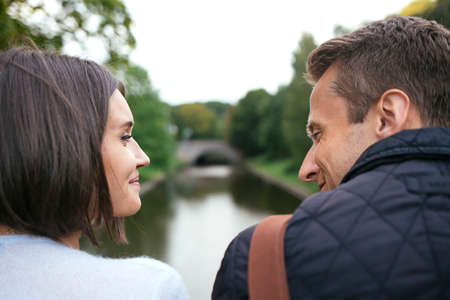 Woman and men in love on bridge walking by the river