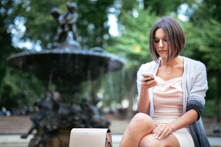 Girl sitting outdoors in the city street texting using cell phone