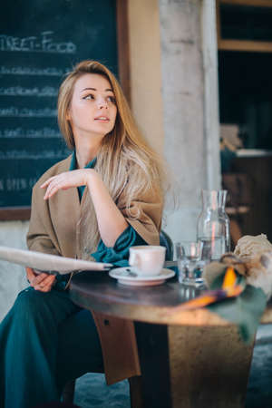 Cafe table customer young woman coffee cup newspaper lifestule