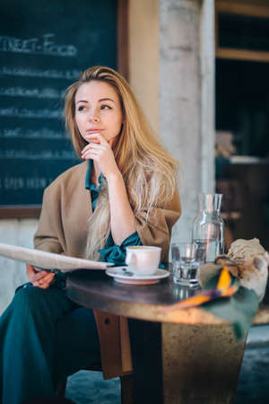 Restaurant table young woman thinking doubt coffee newspaper