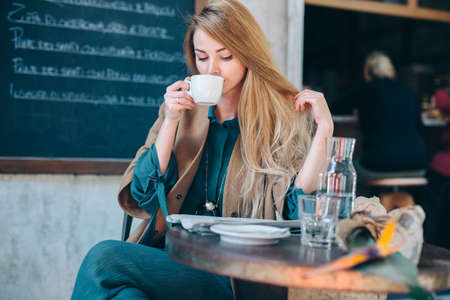 Young blonde woman drinking coffee cup background lifestule