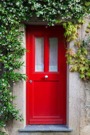 door knob: Close up of a red entrance door with jasmine flowers around  Stock Photo