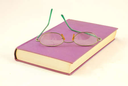 Book and glasses on white background