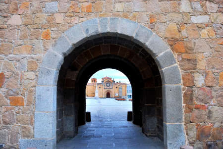Stone arch in the wall of Avila reveals an old church in the distance