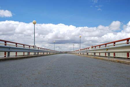 Bridge with street lights under cloudy blue sky
