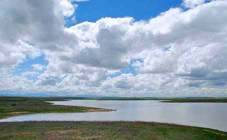 remoteness: Large amounts of water in dam under a cloudy and blue sky