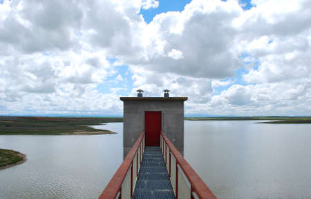 amounts: Large amounts of water in dam under a cloudy and blue sky