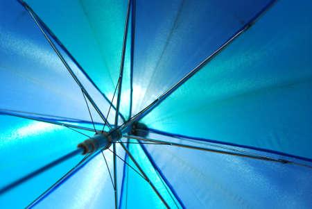 Translucent blue umbrella seen below transparent some light