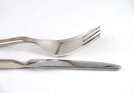 Knife and fork on white tablecloth
