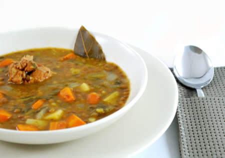 Dish of stewed lentils with meat, bay leaf and carrot  Stock Photo