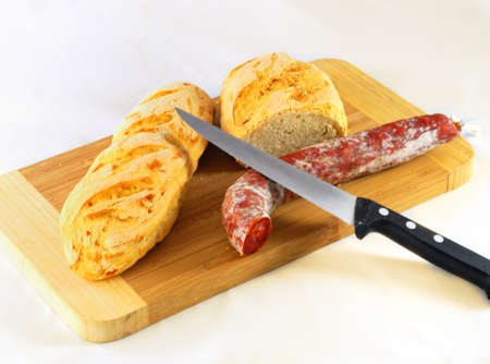 Pieces of bread with sausage and a knife over wood brown table