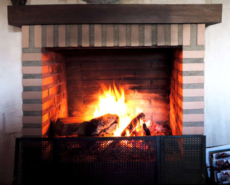 Burning fireplace with firebricks and ornamental wooden beam