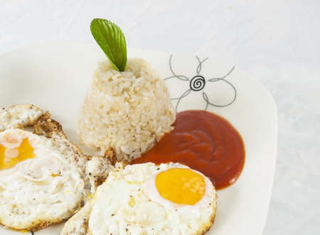 Couple fried eggs with rice and tomato Stock Photo