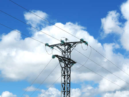 Medium voltage metal tower with green glass insulators backlit on cloudy blue sky