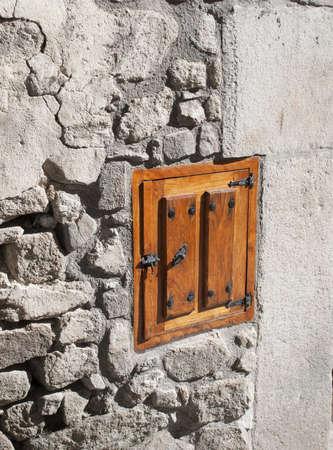 Wooden little window in stone wall Stock Photo
