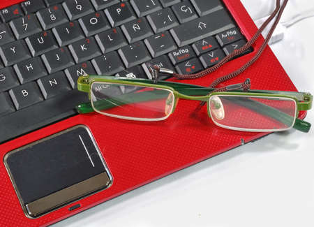 Red laptop and glasses over green tablecloth  Stock Photo