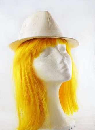 Model of polystyrene yellow wig white hat lit study Stock Photo