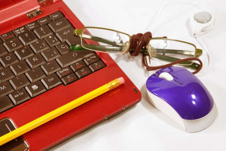 Red laptop and glasses over white tablecloth
