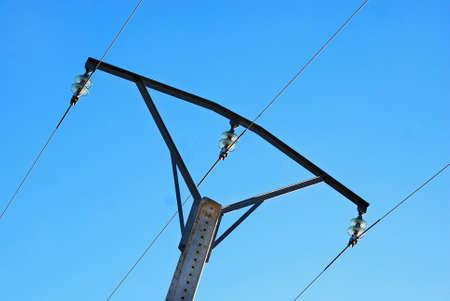 insulators: Medium voltage metal tower with green glass insulators backlit on blue sky Stock Photo