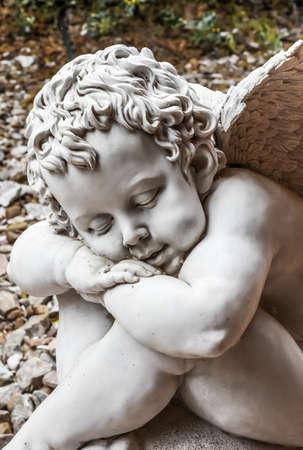Little asleep angel of stone in the garden Stock Photo