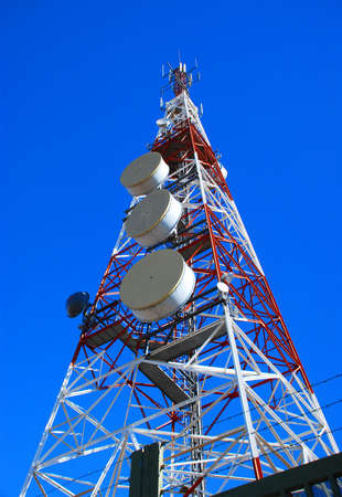 Communications tower in the meadow under blue sky Stock Photo