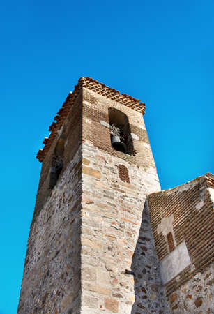Ancient church bell tower in the sun with two bells