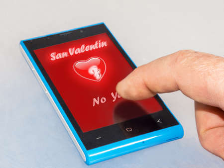 Heart in love on smartphone with finger clicking in yes Stock Photo