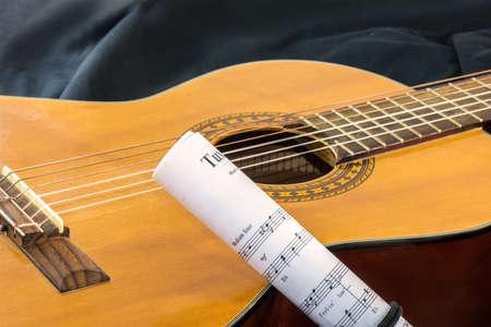 Sheet music and guitar horizontal view on black