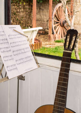 Sheet music and guitar on the window in srping Stock Photo
