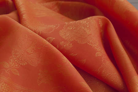 Orange silk with floral oranment Stock Photo