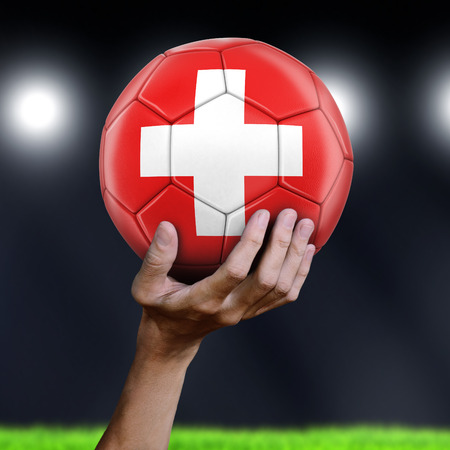 Man holding Soccer ball with Swiss flag