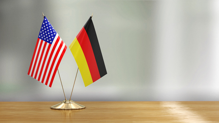 American and German flag pair over defocused background